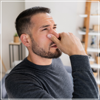 man reacting to bad smell